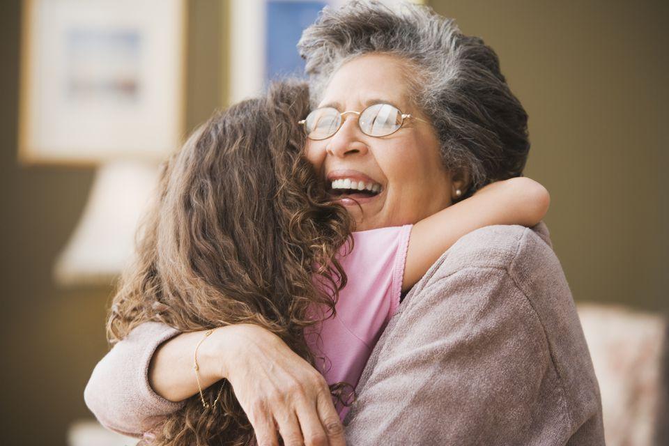 Hispanic grandmother hugging granddaughter