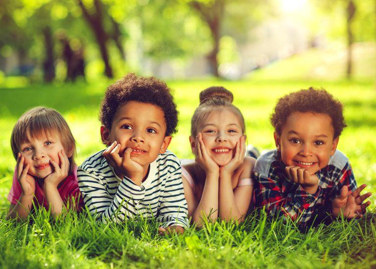 Four children lying on grass