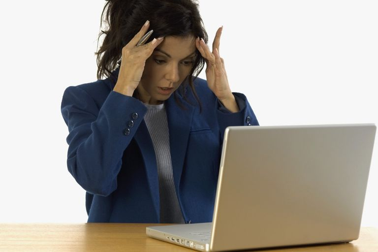Woman looking at computer with shock.