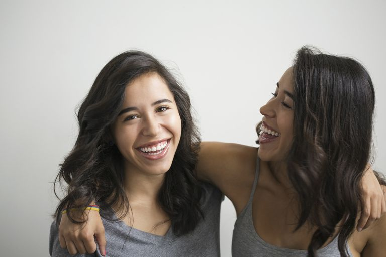 Brunette twin sisters hugging and laughing
