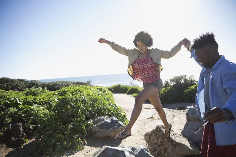 Playful young couple on rocks on sunny beach