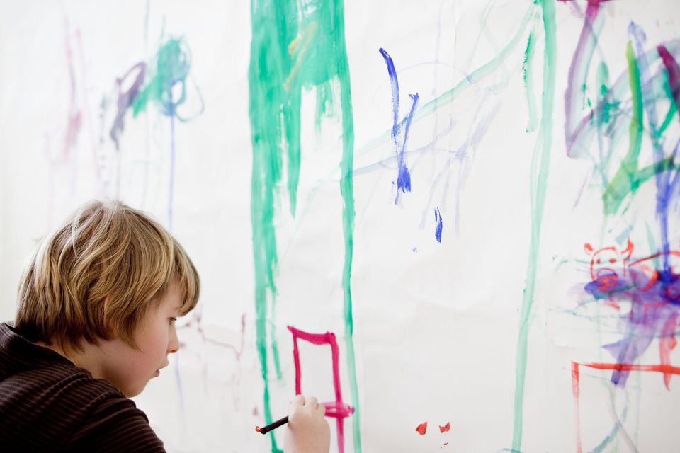 A picture of a boy painting on an indoor canvas