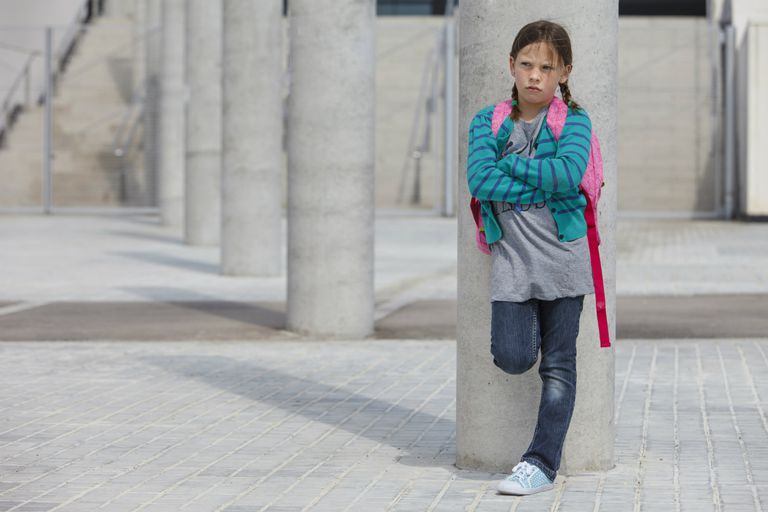 Frowning girl leaning against column
