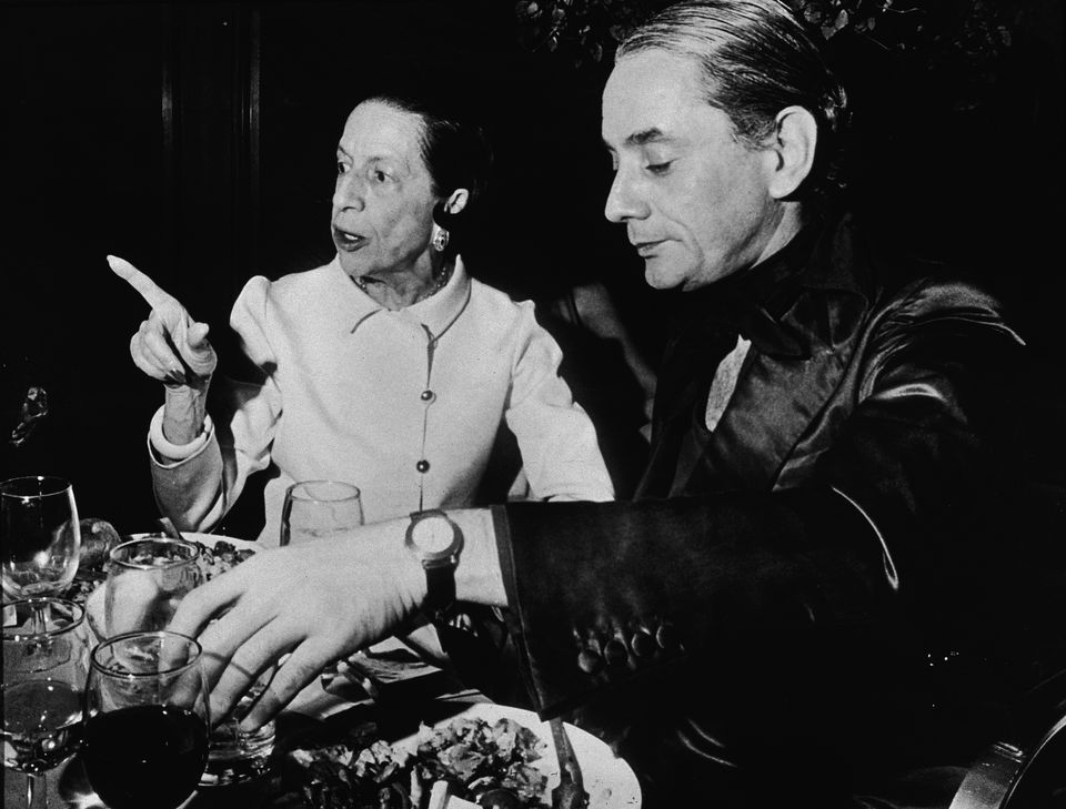 Fashion editor Diana Vreeland (1901 - 1989) and jewelry designer Kenneth Jay Lane sit together during a supper party at the Four Seasons restaurant, New York City, August 11, 1976.