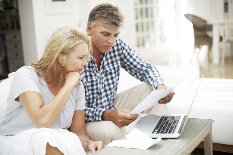 Mature couple doing paperwork and using computer