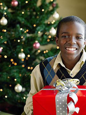 Picture of a boy holding a red gift in front of a Christmas tree