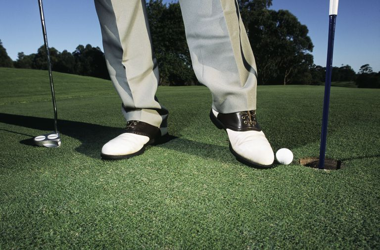 Golfer taps golf ball into the hole using his foot wedge