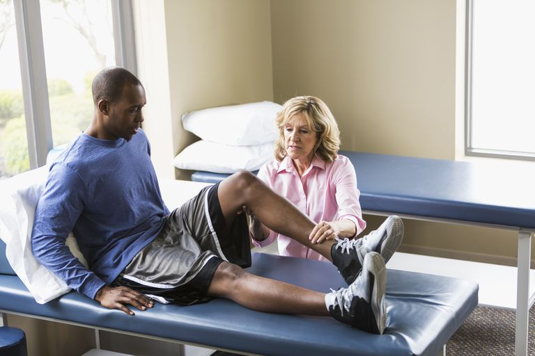 Photo of a woman therapist examining a man's knee.