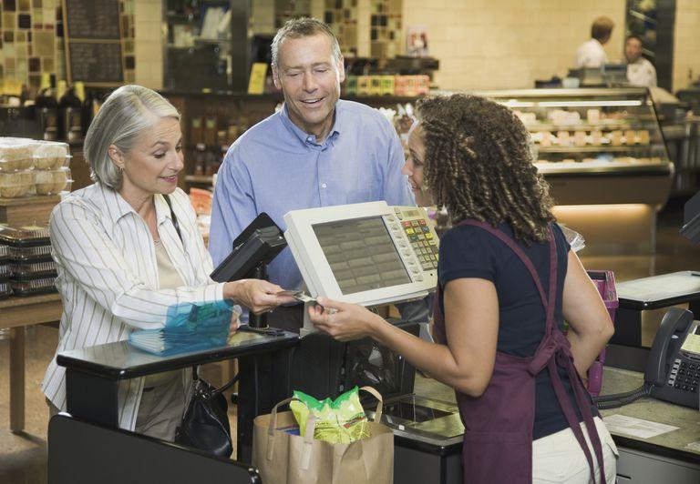 Senior woman paying cashier, mature man watching