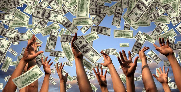 Hands reaching toward falling money.