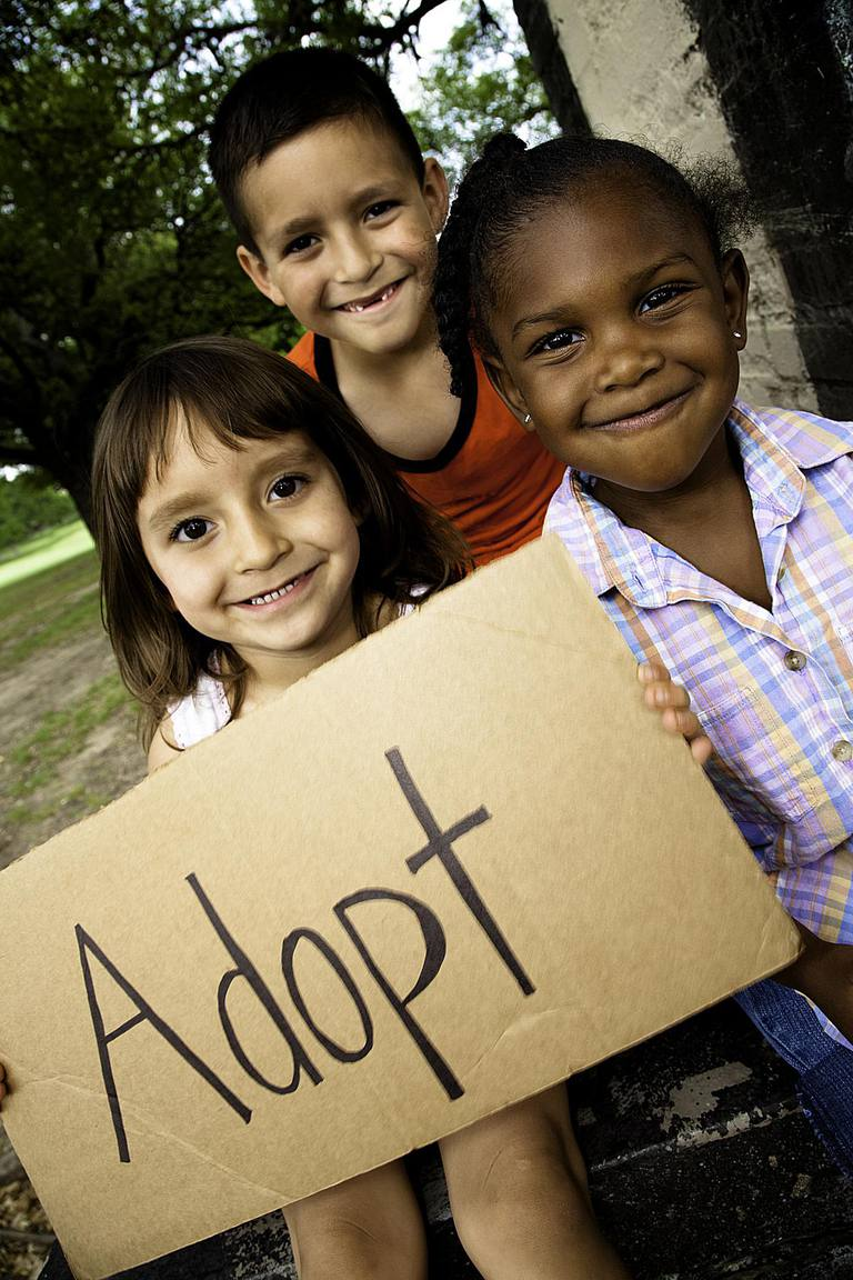 Group of Little Children Holding Sign Reading ADOPT