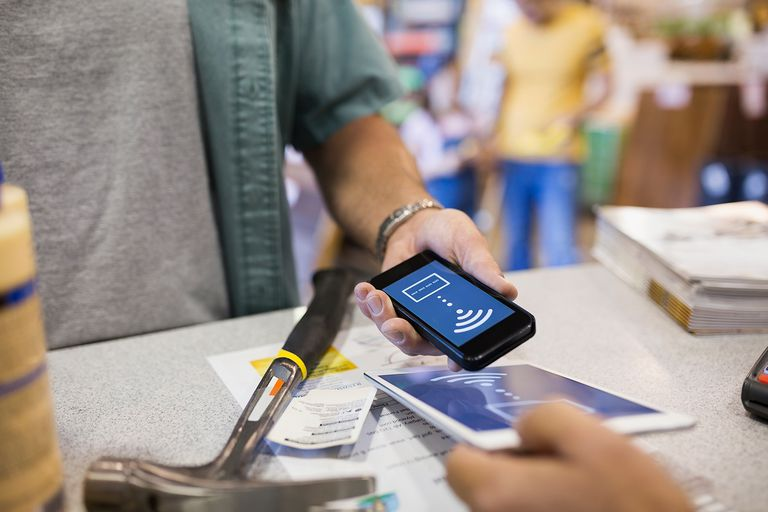 Close up man using contactless payment at home improvement store.