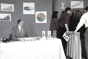 Man at empty trade show booth looking at crowd in next door booth