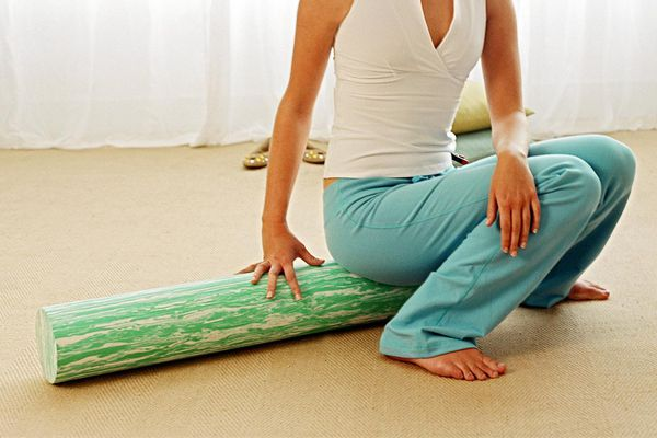 Woman sitting on foam roller