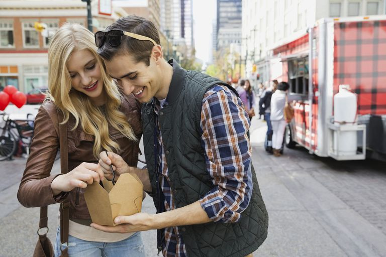 Couple standing outdoors sharing a meal from a food truck