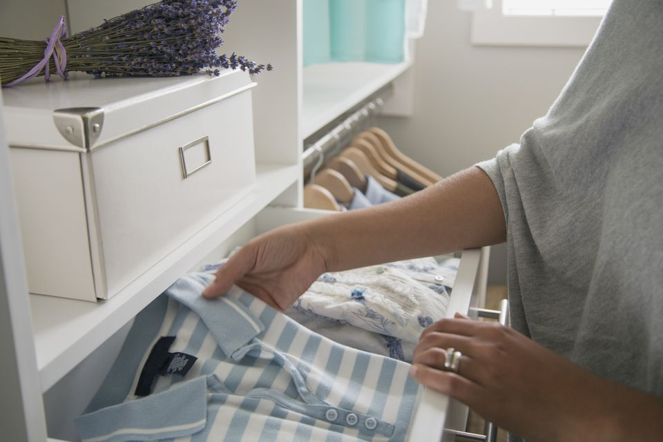 Woman placing clean shirt into drawers.