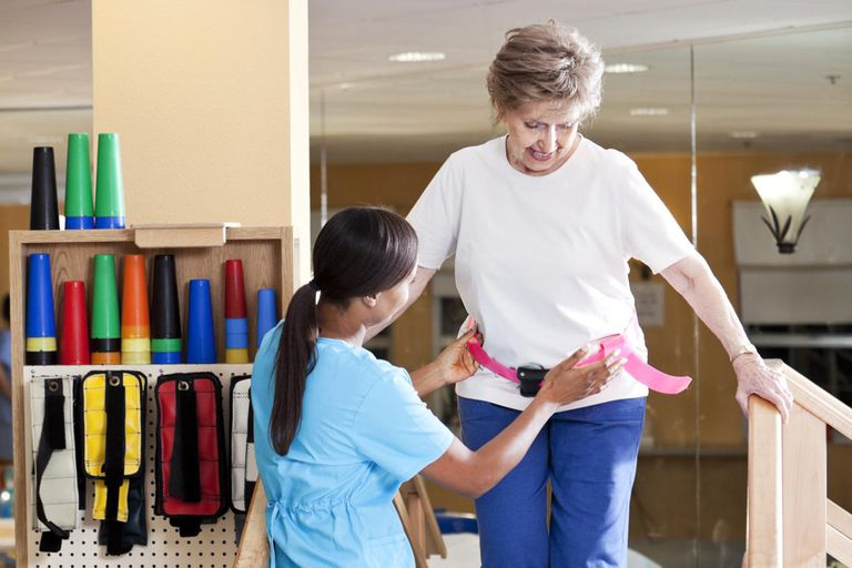 Physical therapist with senior woman climbing stairs