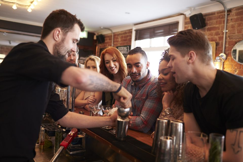 Bartender Giving Cocktail Making Lesson to Friends In Bar