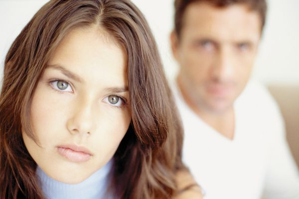 Woman looking sad with a man in the background