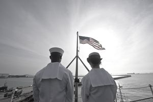 Sailors stand by to lower the ensign as the Nimitz-class aircraft carrier USS John C. Stennis departs Singapore.