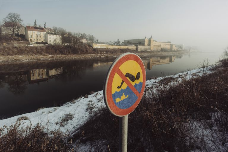 'No swimming sign, St. Augustine and John The Baptist Baroque Church in the background'