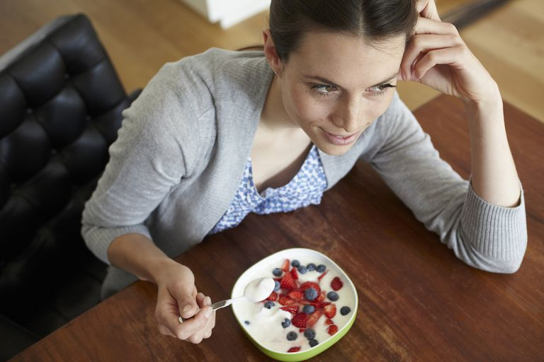 Woman eating bowl of yogurt with blueberries and strawberries