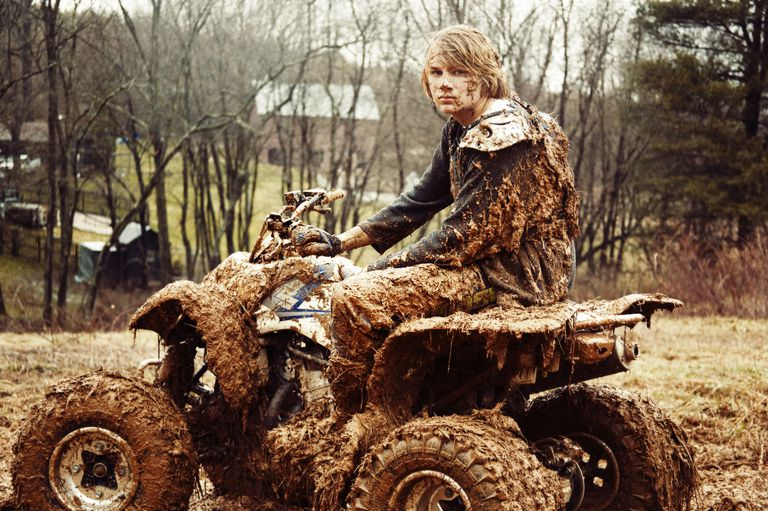 Muddy teenager on a quad