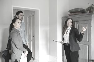 Female realtor pointing while standing with young couple at home