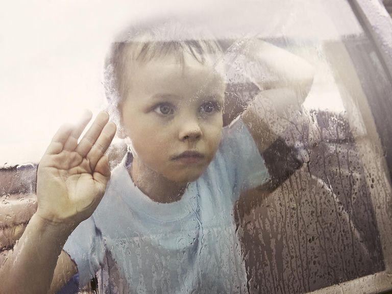 Boy looking out rain-streaked car window