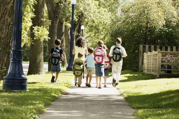 Walking school bus - group of children walking with an adult, wearing backpacks