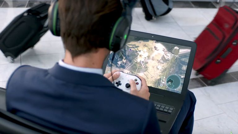 Man in a suit playing a video game via Xbox Play Anywhere on his laptop at an airport