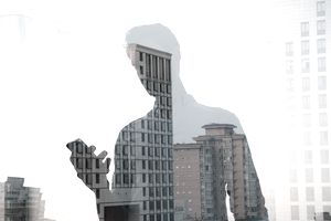 Double exposure of man using mobile phone and city