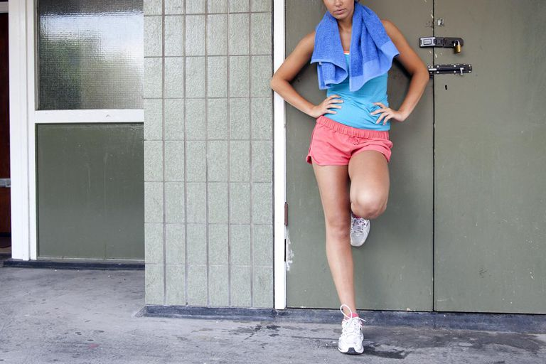 woman in athletic clothes leaning against a door