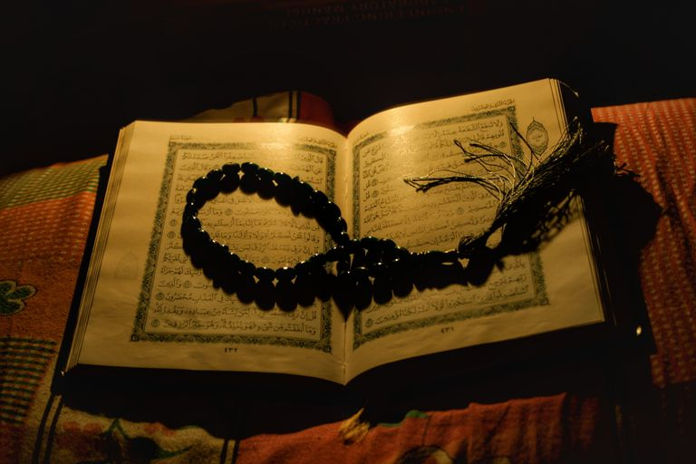 High Angle View Of Koran And Beads On Bed