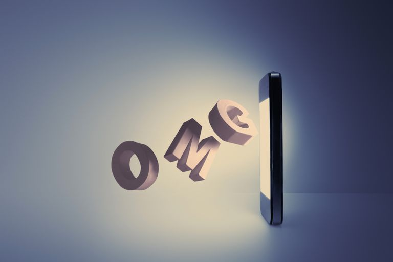 Letters O M G coming out from a cell phone screen, acronym you might find in fertility forums and social media sites