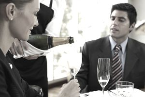 Waiter serving champagne to couple at restaurant