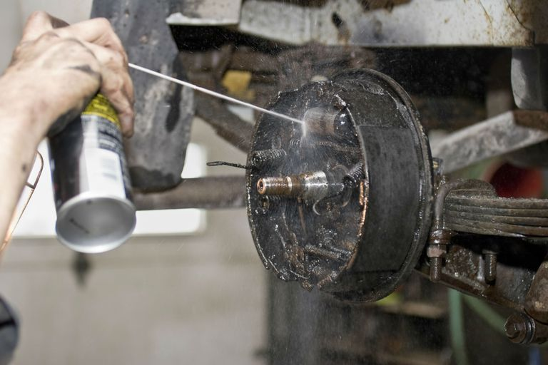 Spraying solvent on a brake drum to clean it.