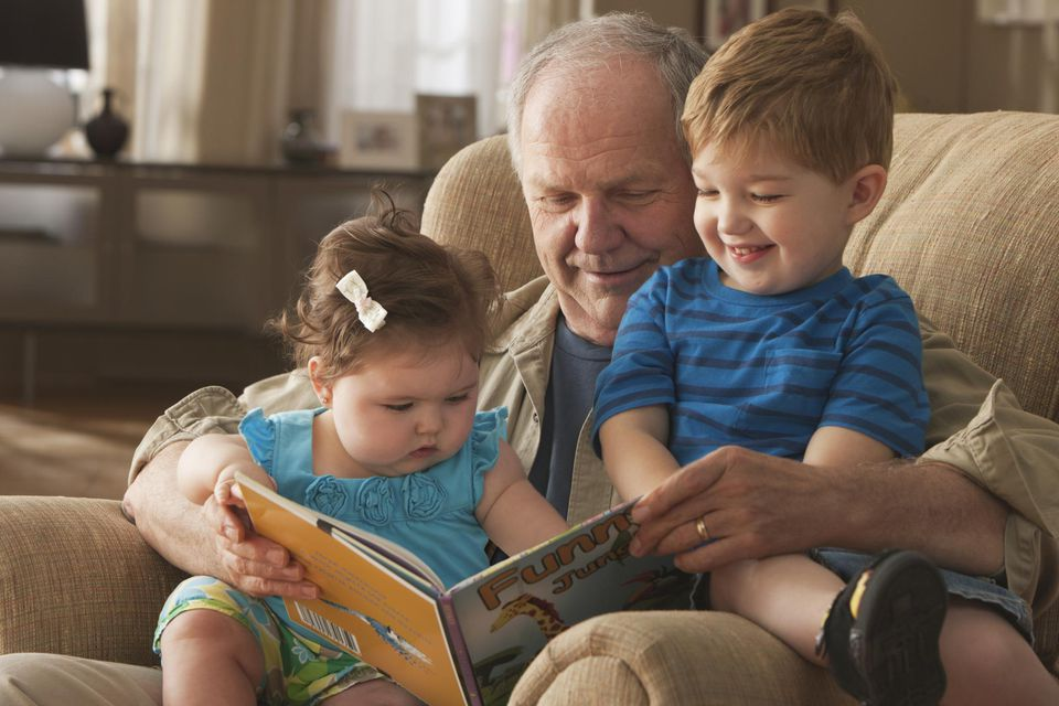 Grandfather reading book to toddler grandchildren