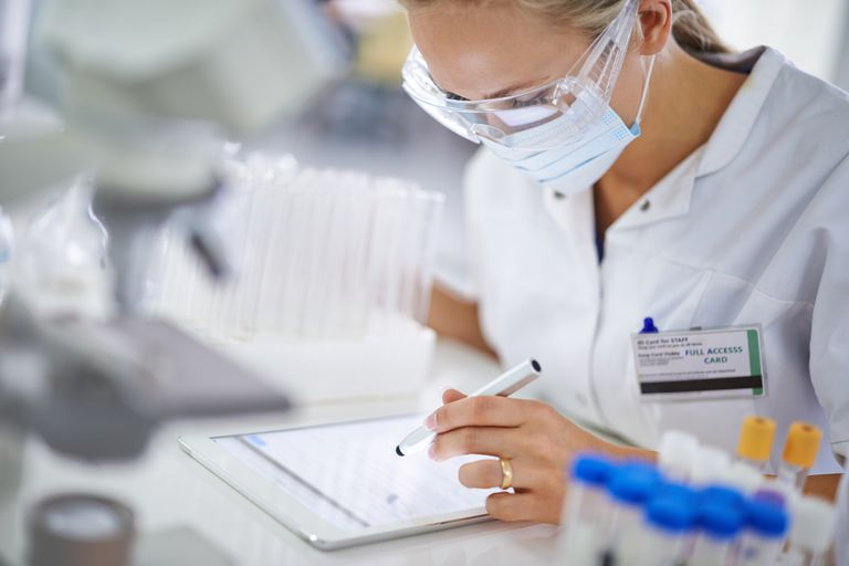 A young researcher recording her findings on a tablet in the lab