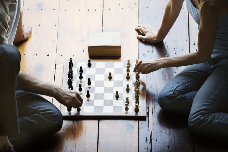 Couple Playing Chess Together on Wood Floor