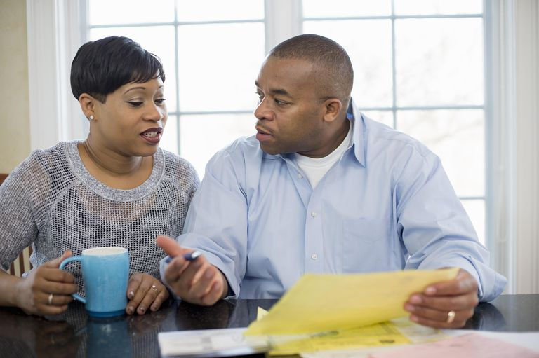 Couple sitting at kitchen table discussing bills