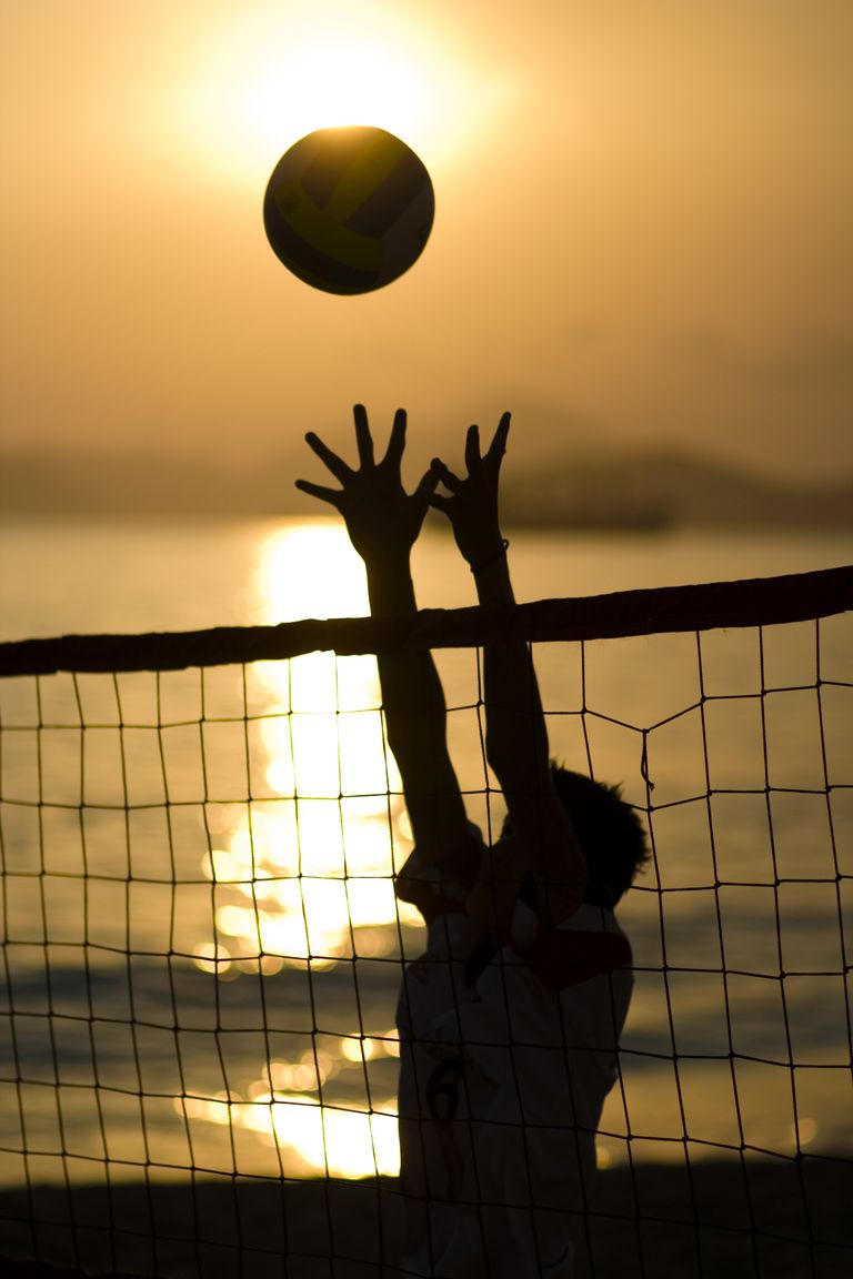 Silhouette of a person playing beach volleyball