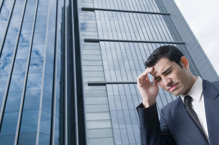 Low angle view of a businessman suffering from a headache
