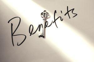 Light shining on skeleton key and handwritten word 'Benefits'.