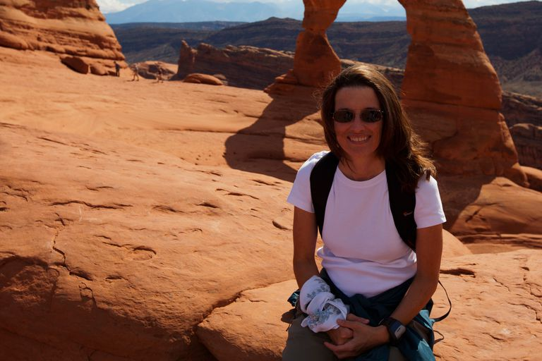 Laura Klappenbach, stopping for a photo in front of Delicate Arch, Arches National Park, Utah.
