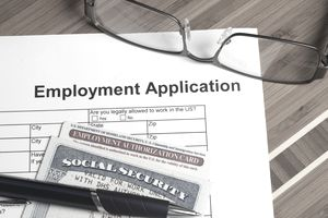 a job application with a pen and SSN card resting on it
