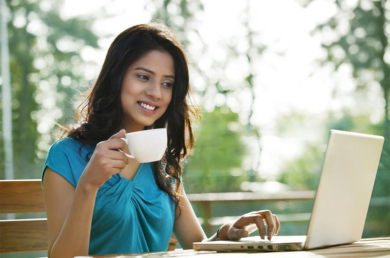 Beautiful young woman having coffee while using laptop at sidewalk cafe