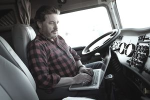 Truck driver working on laptop computer inside cab of semi truck