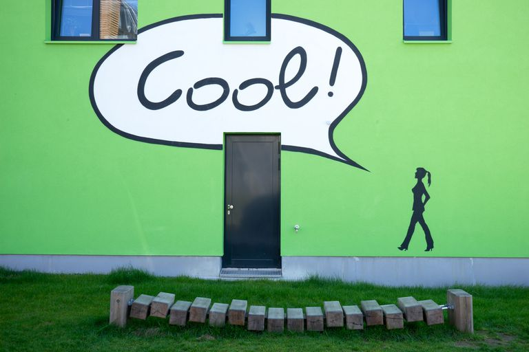 """Green apartment building with painted figure with voice balloon that says """"Cool!"""""""