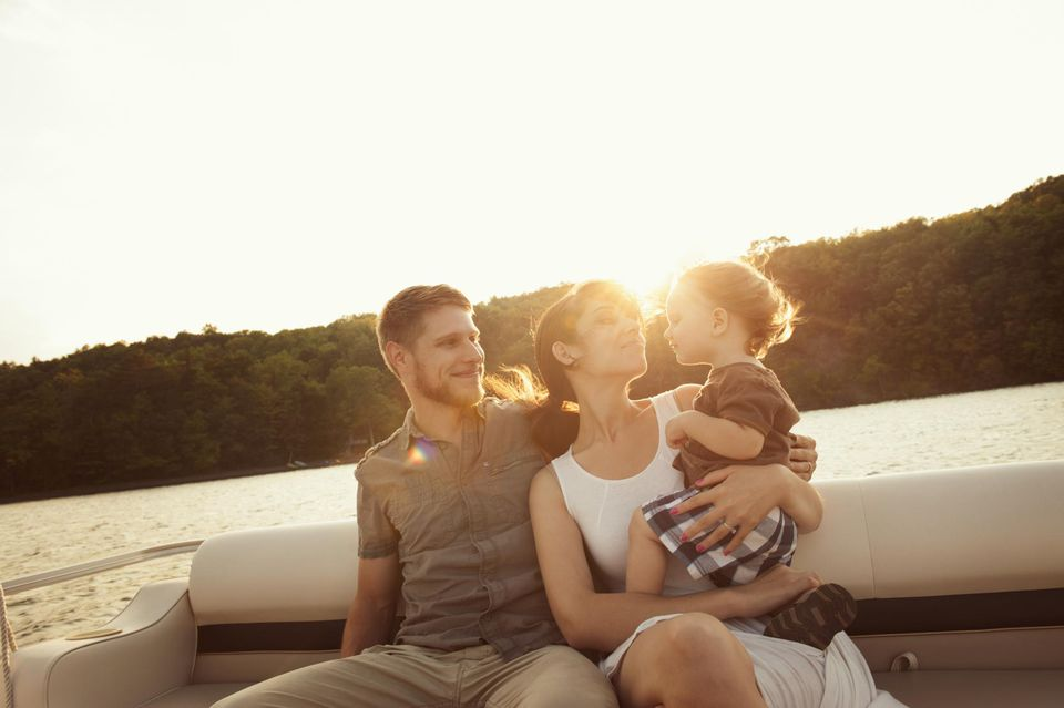 Young Family Riding On Boat At Sunset